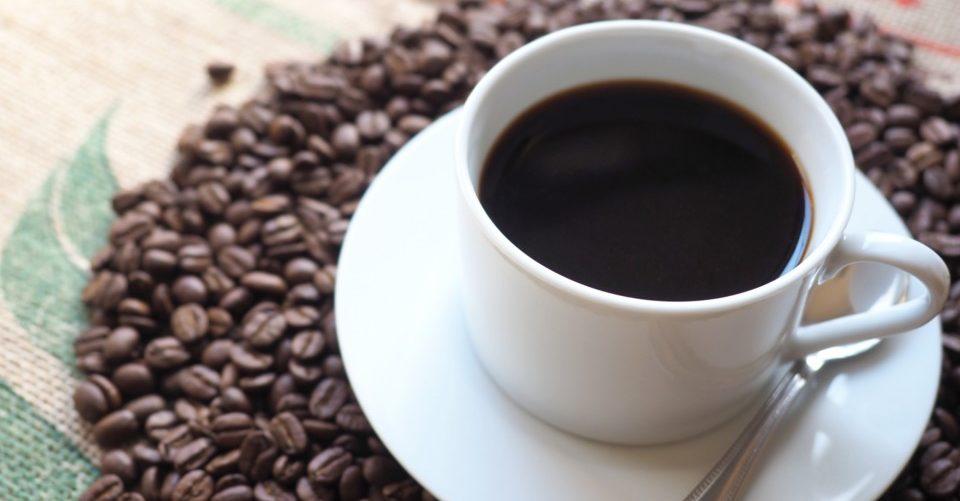 コーヒー豆の上にコーヒーの入ったカップが乗っているところ